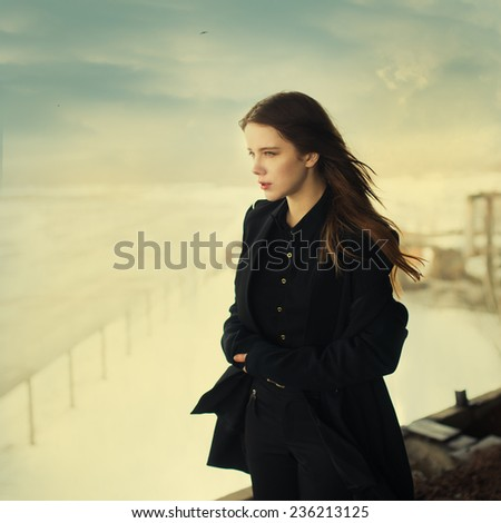beautiful young woman high above the ground in windy weather - stock photo
