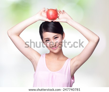 Beautiful young woman hold red apple with charming smile. Isolated over nature green background, asian beauty - stock photo