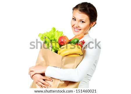 Beautiful young woman holding a bag with fresh fruits and vegetables. Healthy eating. Isolated over white.