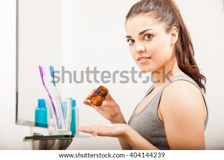 Beautiful young woman holding a bottle of pills and vitamins to take in the morning in a bathroom - stock photo