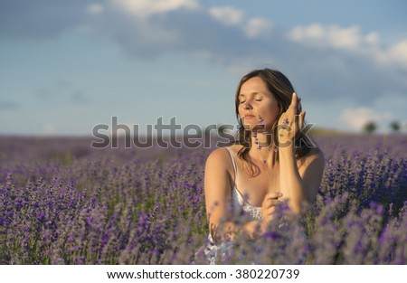 Beautiful young woman holding a bunch of lavender flowers enjoying their fragrance in the middle of a lanvender field at sunset. - stock photo