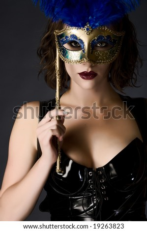 Beautiful young woman holding a carnival mask wearing catsuit - stock photo