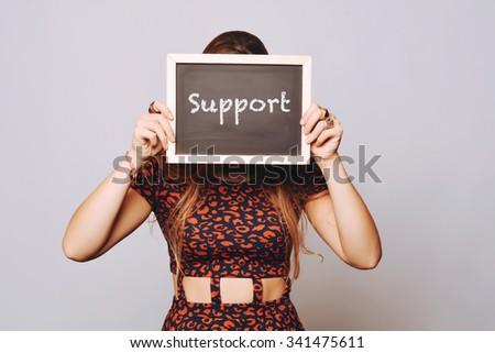 Beautiful young woman holding a chalkboard / blackboard saying support. Caucasian young girl. - stock photo