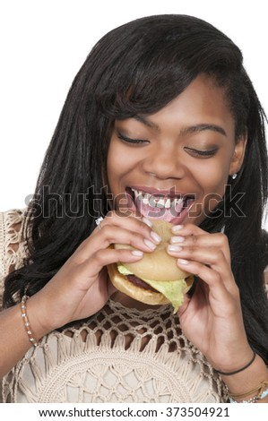 Beautiful young woman holding a delicious cheeseburger - stock photo