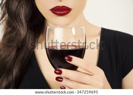beautiful young woman holding a glass of red wine, focus on lips, closeup portrait