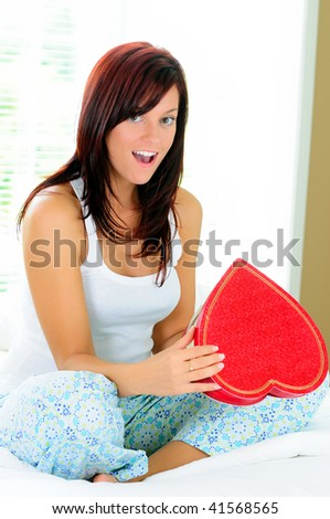 Beautiful Young Woman Holding A Heart Shaped Box Of Chocolates Surprised By It's Contents - stock photo
