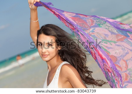 Beautiful young woman holding a purple shawl against the ocean breeze enjoying the South Beach shoreline in Miami. - stock photo
