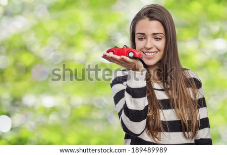 Beautiful young woman holding a red car - stock photo