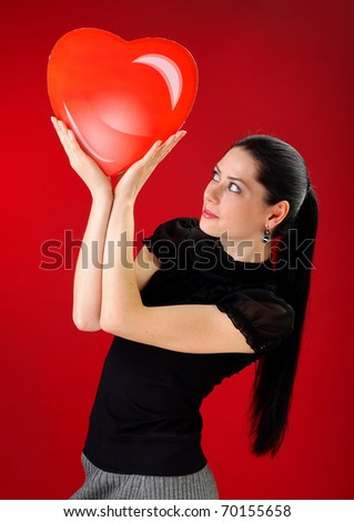 Beautiful young woman holding a red heart; Valentine concept - stock photo