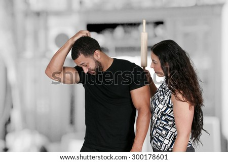 Beautiful young woman holding a rolling pin with a man - stock photo