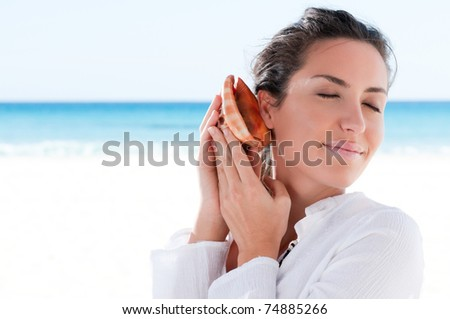 Beautiful young woman holding a shell and dreaming a summer vacation - stock photo