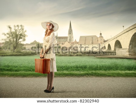 Beautiful young woman holding a suitcase with village in the background