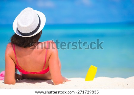 Beautiful young woman holding a suncream lying on tropical beach - stock photo
