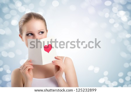 beautiful young woman holding a valentine postcard with a pink heart on abstract background - stock photo