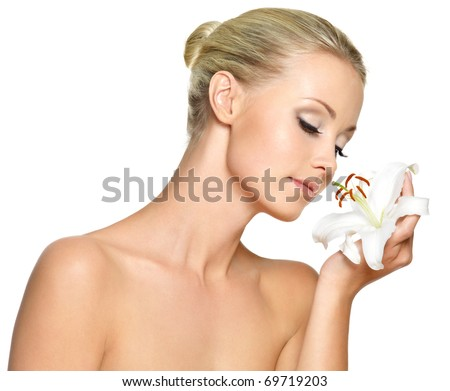 Beautiful young woman holding  a white lily at face, isolated on white - stock photo