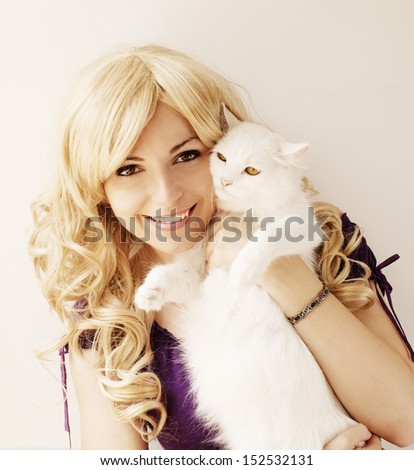 Beautiful young woman holding an adorable white cat - stock photo