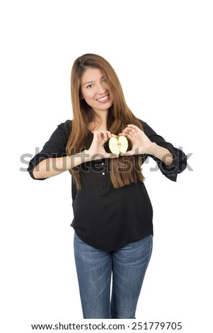 Beautiful young woman holding an apple as her heart against a white background - stock photo