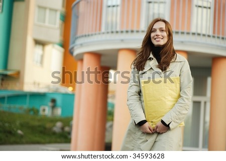 beautiful young woman holding an envelope standing on natural background - stock photo