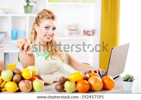 Beautiful young woman holding apple and reading recipe with laptop in a kitchen. Looking at camera.