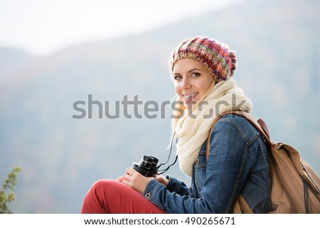 Beautiful young woman holding binoculars, colorful sunny autumn