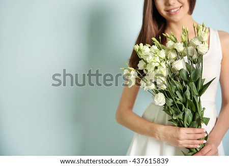 Beautiful young woman holding bouquet of white flowers on light background