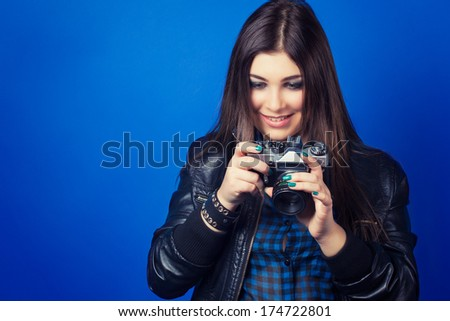 beautiful young woman holding camera on blue background - stock photo