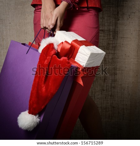 Beautiful young woman holding colored shopping bags, gift box and Santa's hat over canvas background, glamour shopping concept, image toned  - stock photo