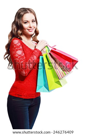 beautiful young woman holding colored shopping bags, over white