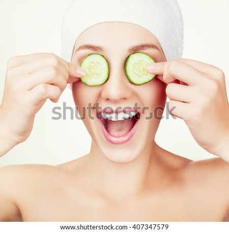 Beautiful young woman holding cucumber slices on her eyes - stock photo