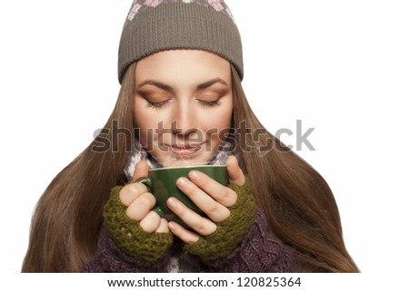 beautiful young woman holding cup of tea or coffee in her hands,wearing knitted clothes.isolated on white