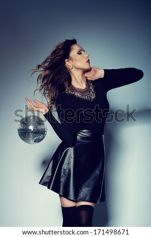 Beautiful young woman holding disco ball