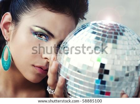 Beautiful young woman holding disco ball - stock photo