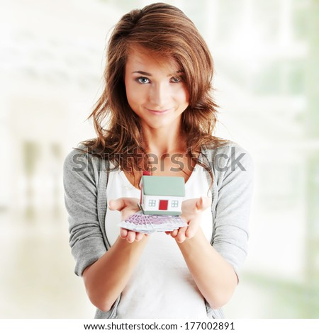 Beautiful young woman holding euros bills and house model over white - real estate loan concept - stock photo