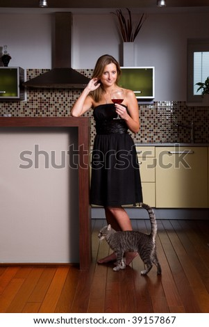 beautiful young woman holding glass of red wine with cat underfoot in modern interior - stock photo
