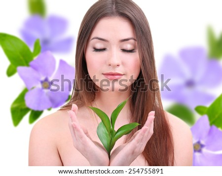Beautiful young woman holding green leaves on purple flower background - stock photo