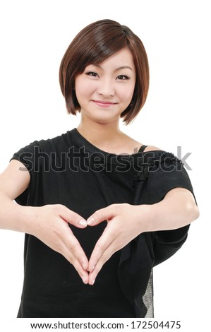 Beautiful young woman holding her hands in heart shape - stock photo