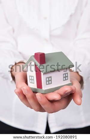 Beautiful young woman holding house model over white - real estate loan concept