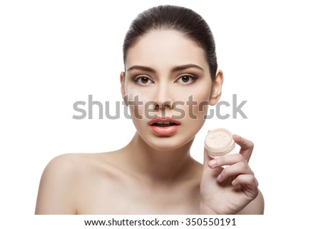 Beautiful young woman holding jar with loose powder near face. Isolated over white background. Copy space. - stock photo