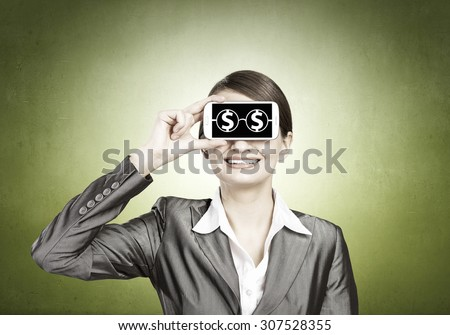 Beautiful young woman holding mobile phone against her eyes - stock photo