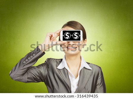 Beautiful young woman holding mobile phone against her eyes and smiling  - stock photo