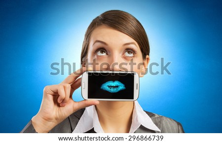 Beautiful young woman holding mobile phone against her mouth and smiling  - stock photo