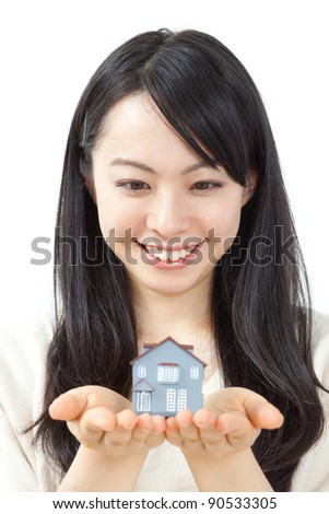 beautiful young woman holding model house isolated on white background