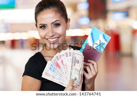 beautiful young woman holding passport, air ticket and cash at airport - stock photo