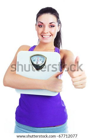 beautiful young woman  holding scales with her thumb up - stock photo
