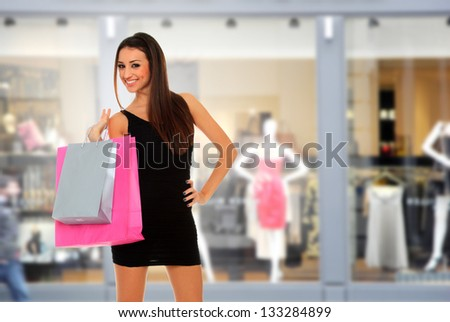 Beautiful young woman holding shopping bags in front of the shop - stock photo