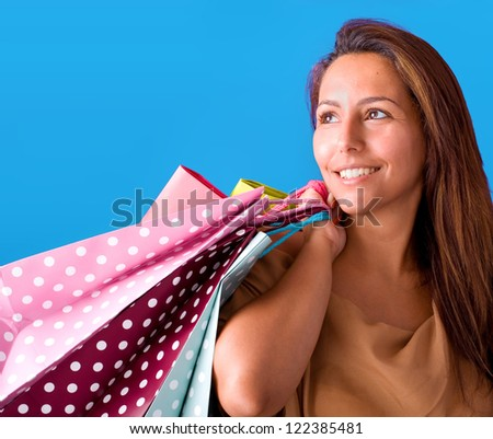 Beautiful young woman holding shopping bags, isolated on blue studio background. - stock photo