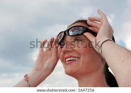 beautiful young woman holding sun glasses up - stock photo