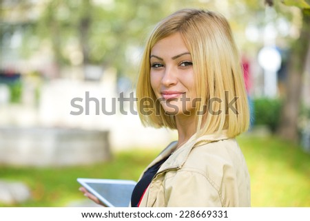Beautiful young woman holding tablet in the park. - stock photo