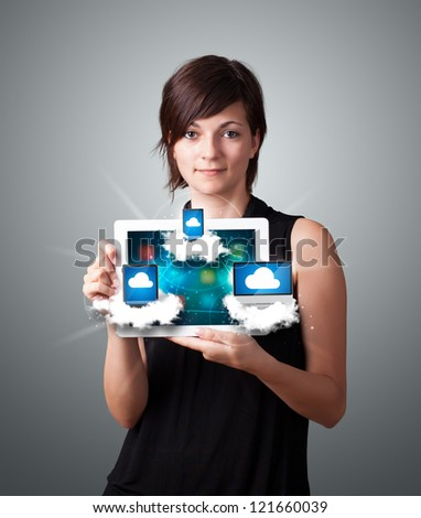 Beautiful young woman holding tablet with modern devices in clouds - stock photo