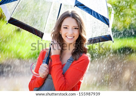 Beautiful young woman holding  umbrella out in the rain - stock photo